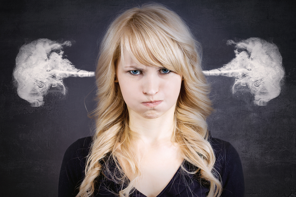 Negative review response, a closeup portrait of angry young woman, blowing steam coming out of ears, about to have nervous atomic breakdown, isolated black background. Negative human emotions facial expression feelings attitude