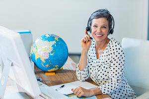 Tour, attractions and travel agent with a headset on by a computer desk.