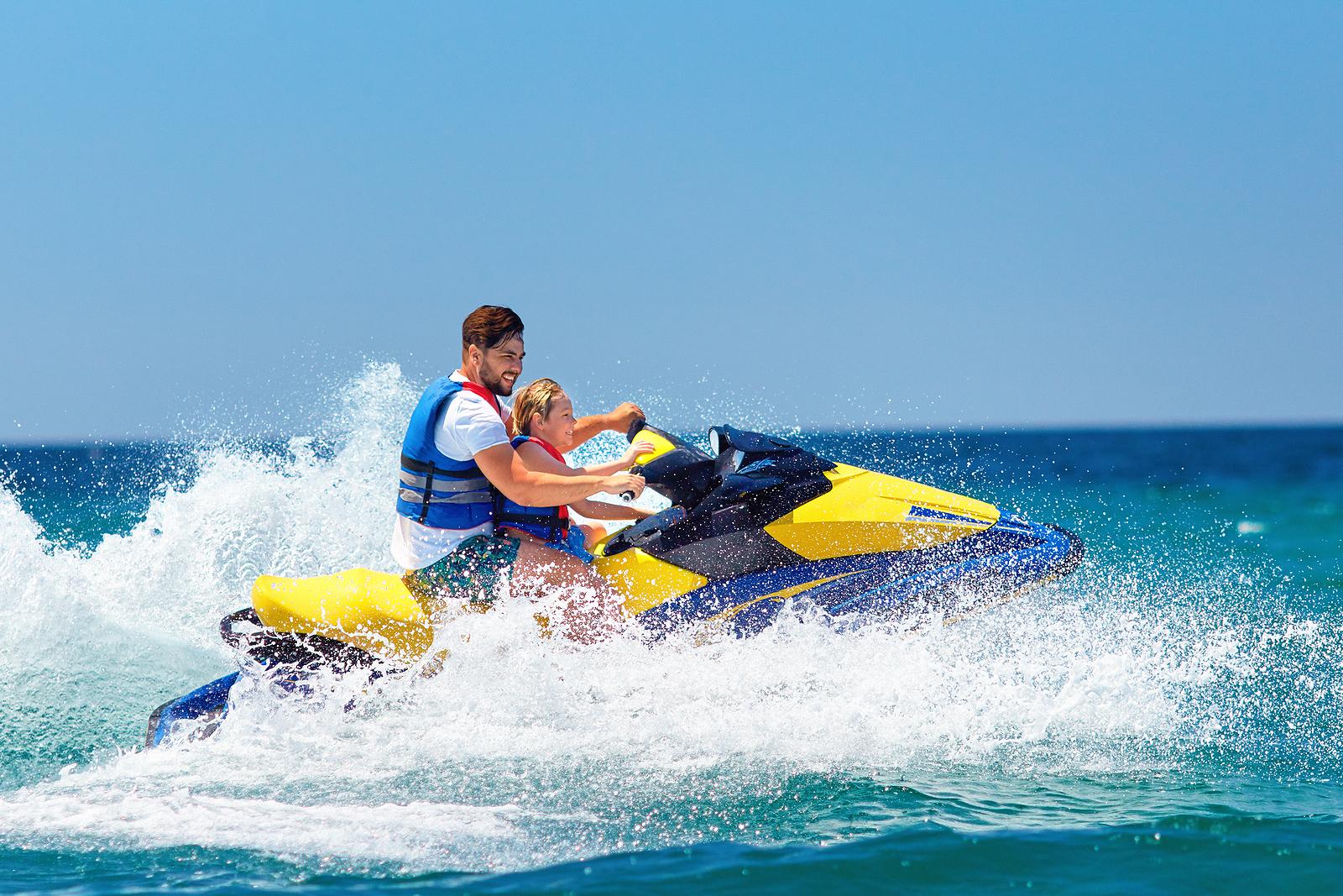 Family on bright yellow jet ski doing tricks on water